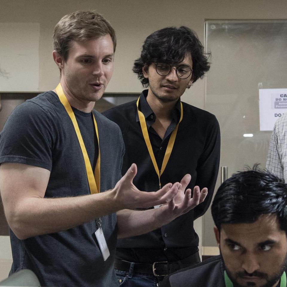 Brian Rieger and Manu Sharma, cofounders of Labelbox, with an unidentified worker at a data annotation company in Delhi, India, before the pandemic.