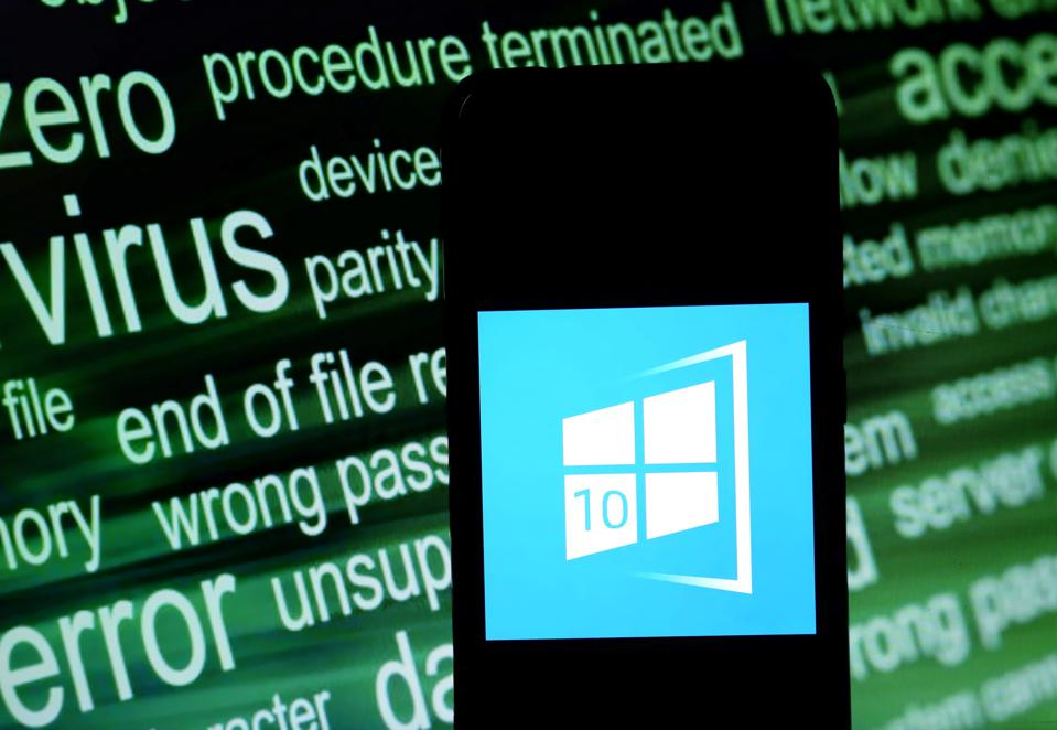 WIndows 10 logo on a smartphone screen in front of a word-cloud of security terms