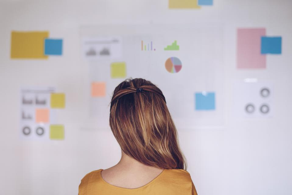 Woman standing in front of chart full of notes