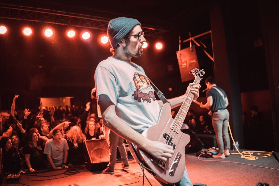 Man in beanie playing bass guitar