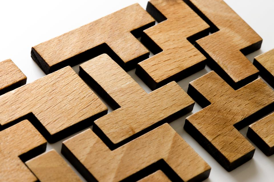 Wooden blocks shaped like Tetris pieces that are fitted together to form a puzzle
