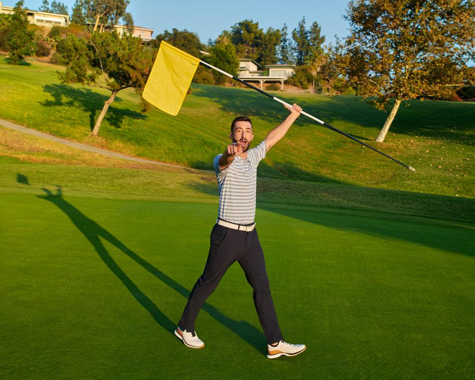 golfer wearing XC4 golf shoes lifts flag stick.