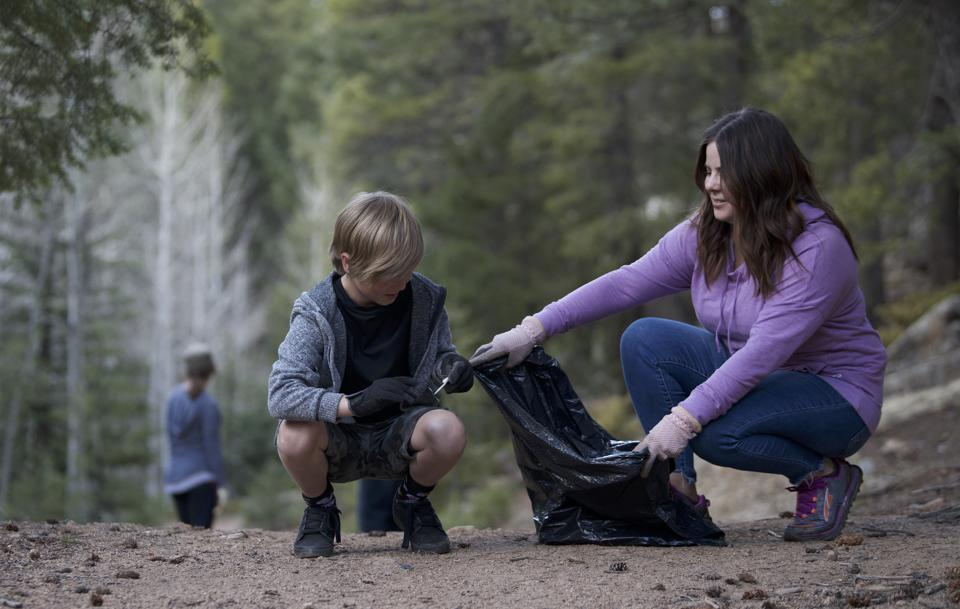 Mother and son collecting discarded items on a hike