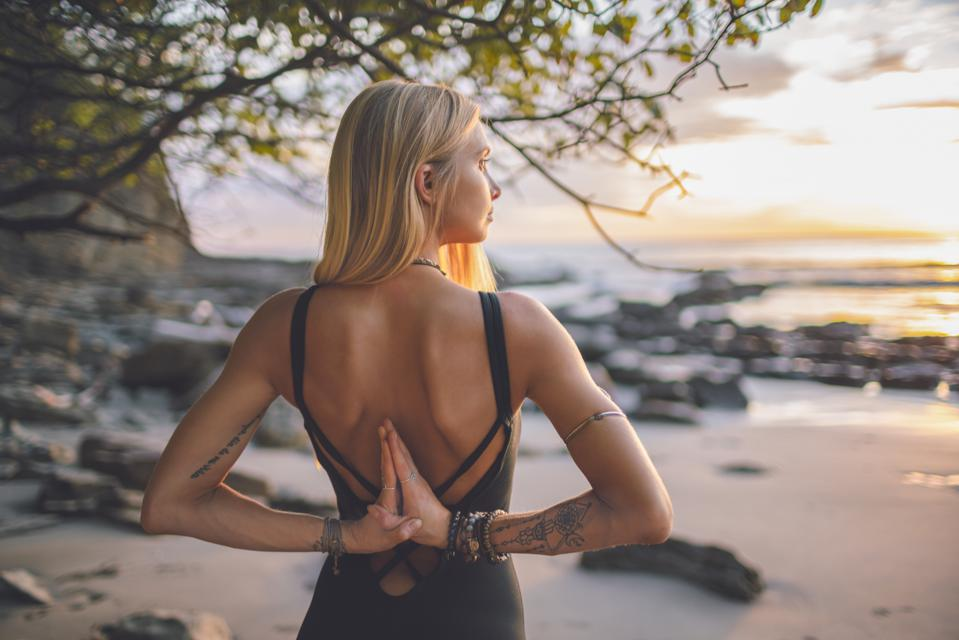 Woman stands on beach at sunset with hands in prayer behind her back and meditates