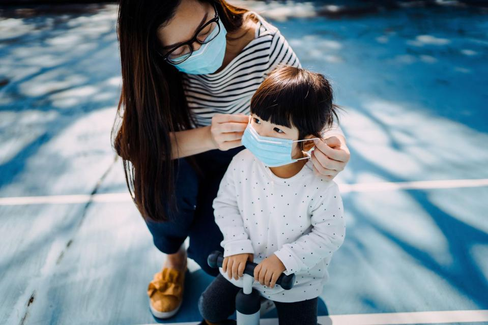 A mom wearing a mask helps a child put a mask on.