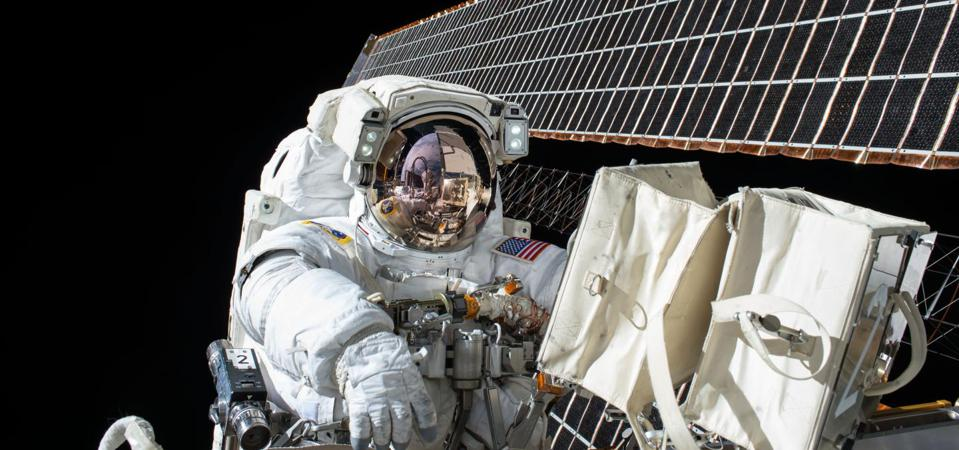 This is Scott Kelly at work on ISS maintenance with the station's solar arrays visible in the background.