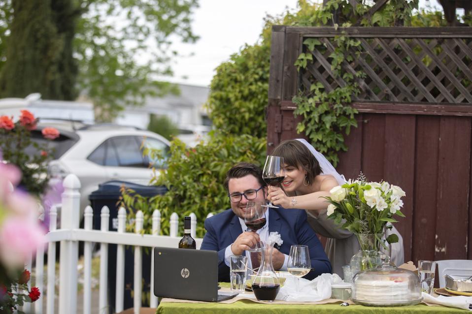 Une mariée et un marié font griller un ordinateur lors de leur mariage virtuel.