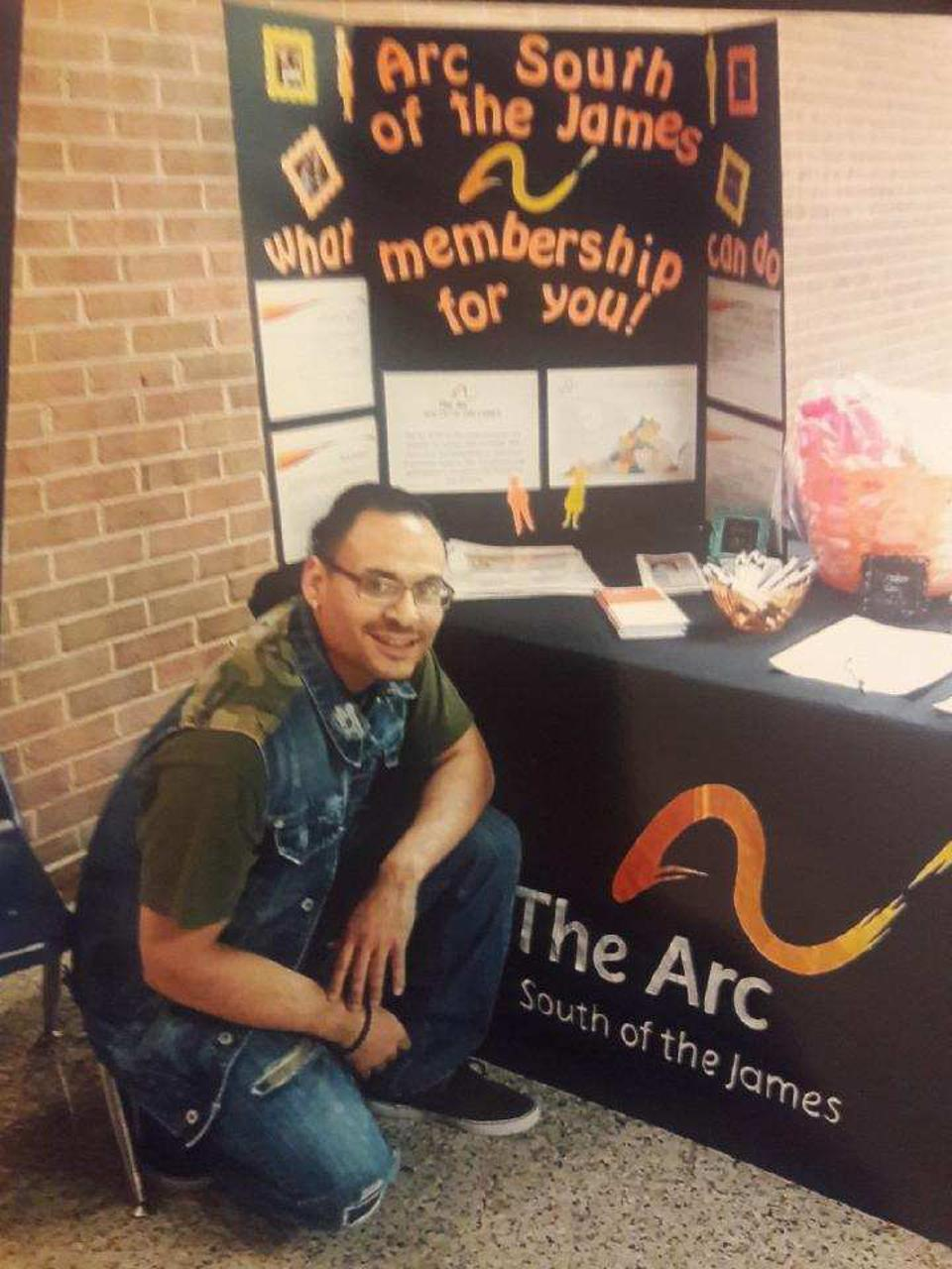 Richard Cuevas kneeling in front of a booth for The Arc South of the James, his self advocacy group.