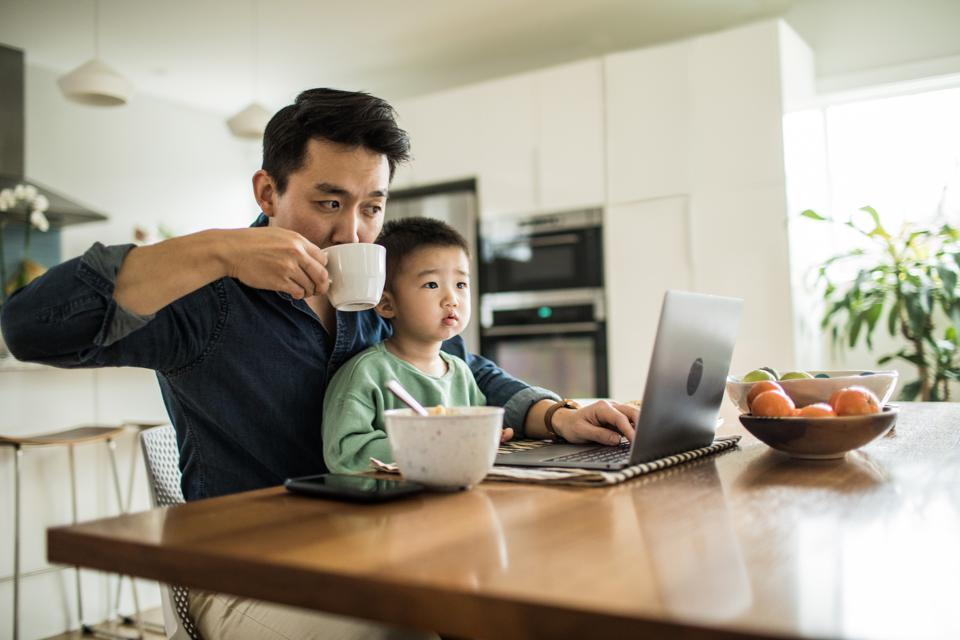 Father multi-tasking with young son (2 yrs) at kitchen table.