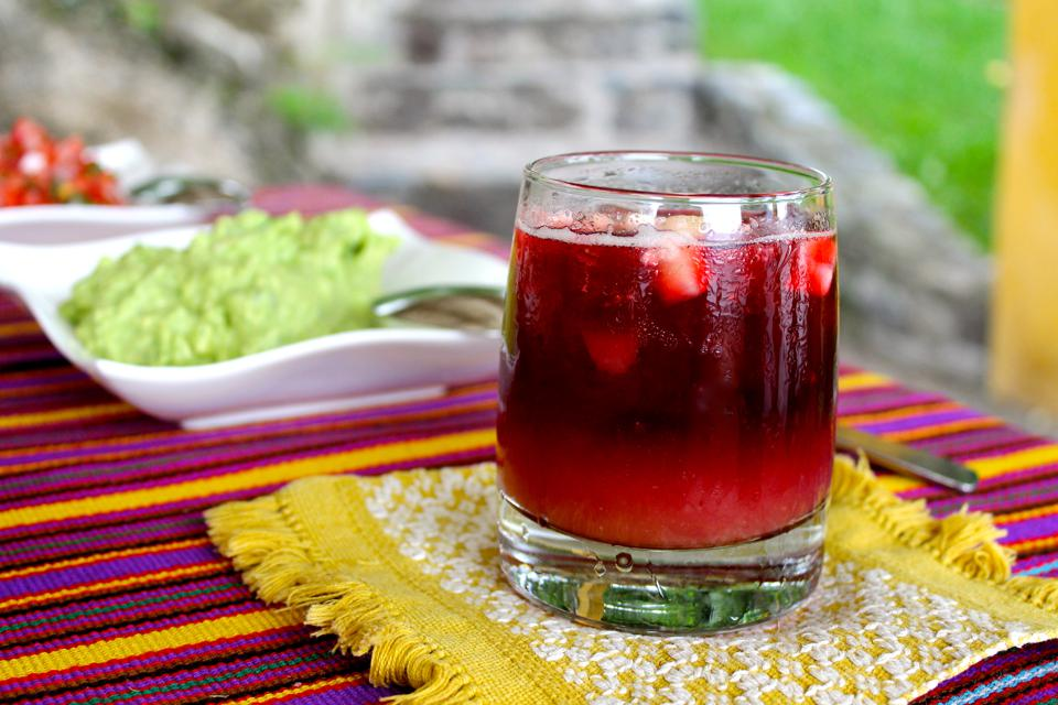 A glass of Rosa Palopo on Guatemalan textiles