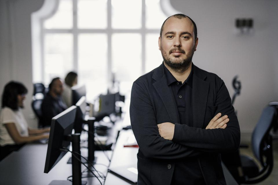 Amuse CEO Diego Farias standing with his arms folded in an office.