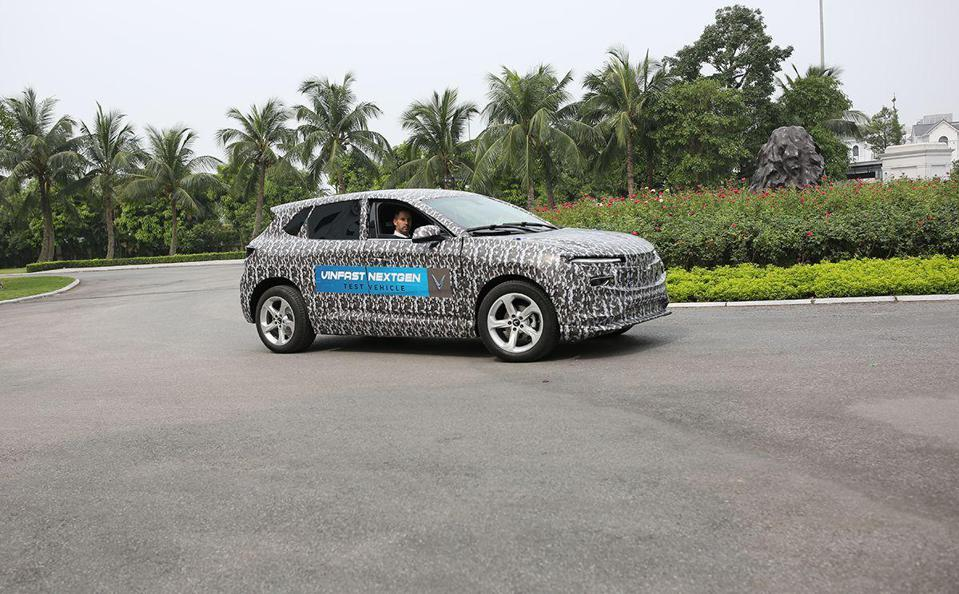 A black and white electric sedan takes a curve during a test run in Hanoi.