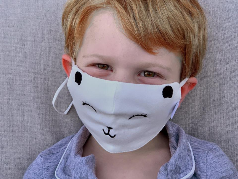 A child in a Paper Cape mask that looks like a bear face