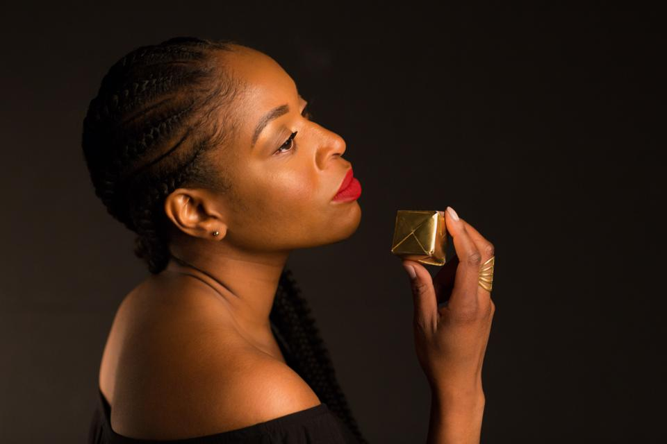 Joy Ike is holding a cube while her head is titled to the side.