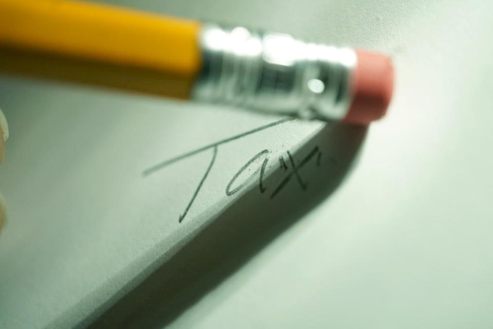 Erasing taxes,pencil erasing tax burden.