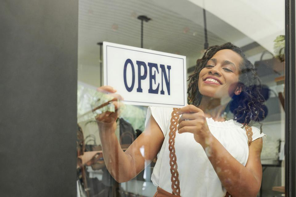 A business owner places an open sign in the store window.