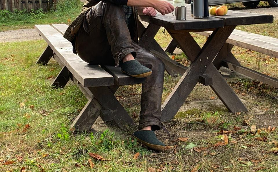 A man wears a pair of Glerups at a picnic table