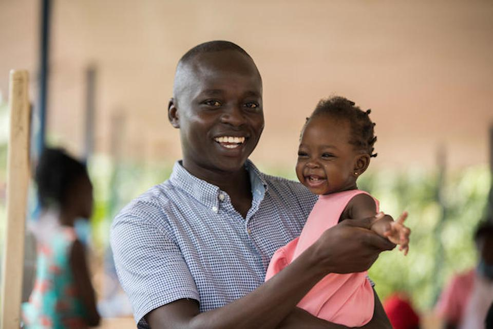 A father in Uganda brings his daughter to get immunized at a UNICEF-supported facility.