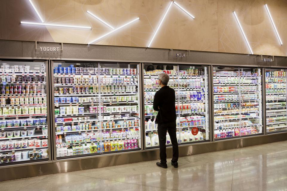 A customer browses the dairy section of a Whole Foods store.