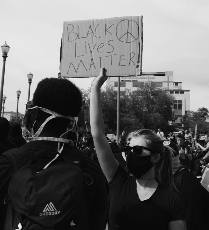 Masked white woman at a protest holding up a Black Lives Matter! placard