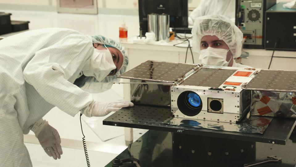 Left to right: Electrical Test Engineer Esha Murty and Integration and Test Lead Cody Colley prepare the ASTERIA spacecraft for mass-properties measurements in April 2017 prior to spacecraft delivery ahead of launch. ASTERIA was deployed from the International Space Station in November 2017.