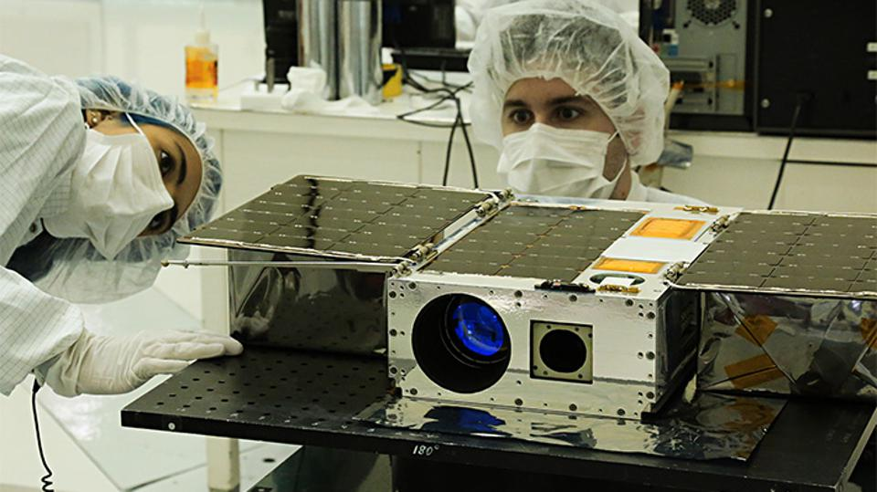 Color photo of two people in PPE working on a cubesat.
