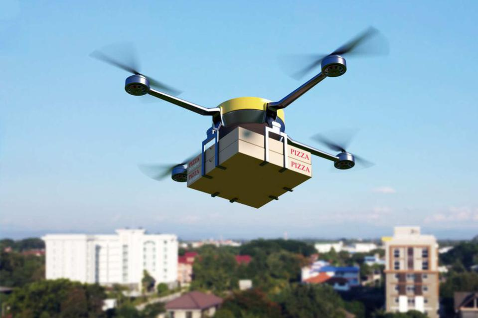 A drone in flight carrying two pizza boxes