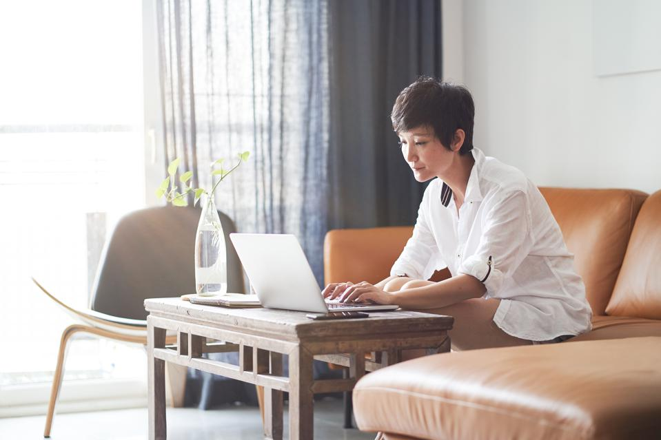 Female professional on computer in living room -- promote your career while working from home