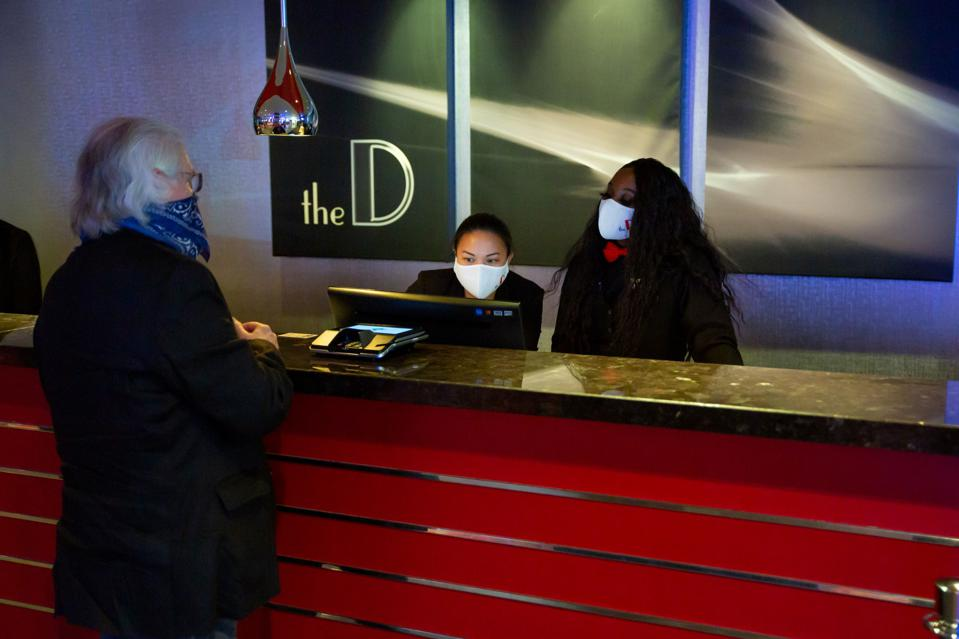 Two masked receptionists and a guest at D Las Vegas check-in