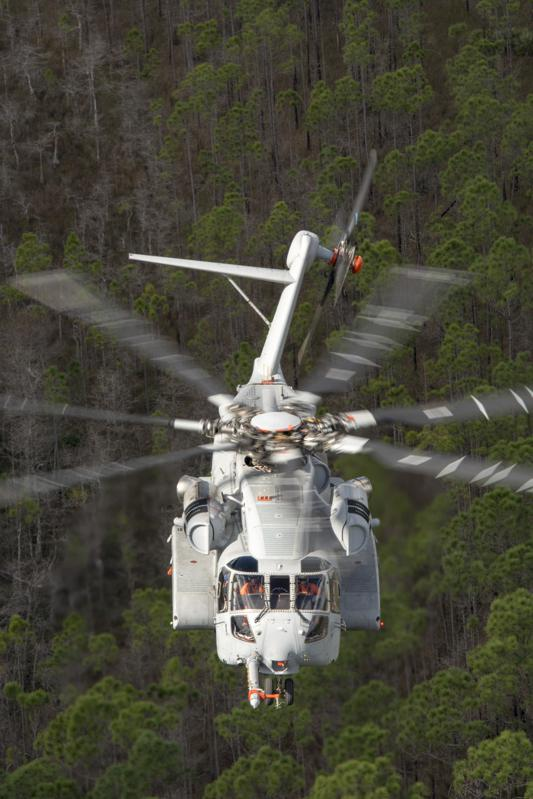 A Ch-53K low over the trees.