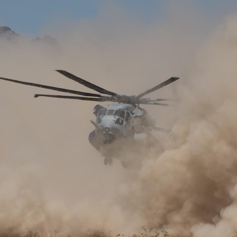 A CH-53K kick up dust as it lowers to a hover.