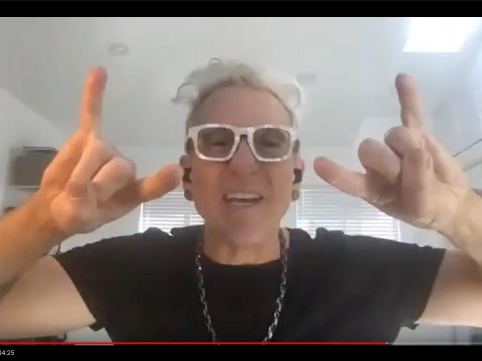 Schulman screenshot, making the symbol for rock and roll with his hands.