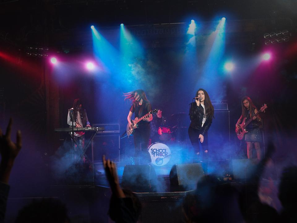 Rock and roll students performing on stage with blue and pink lights.