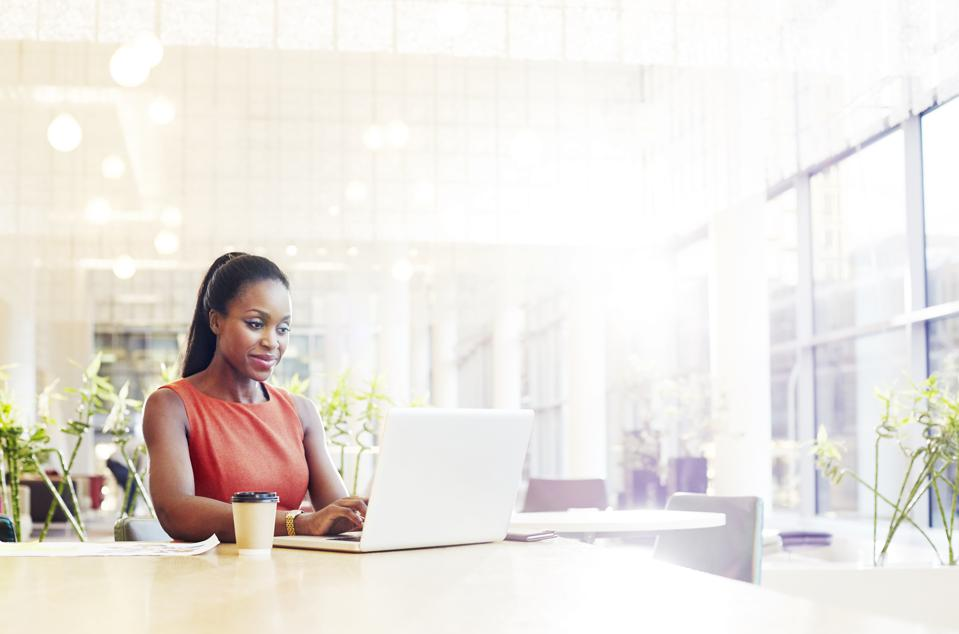 Businesswoman in a modern office using her laptop.