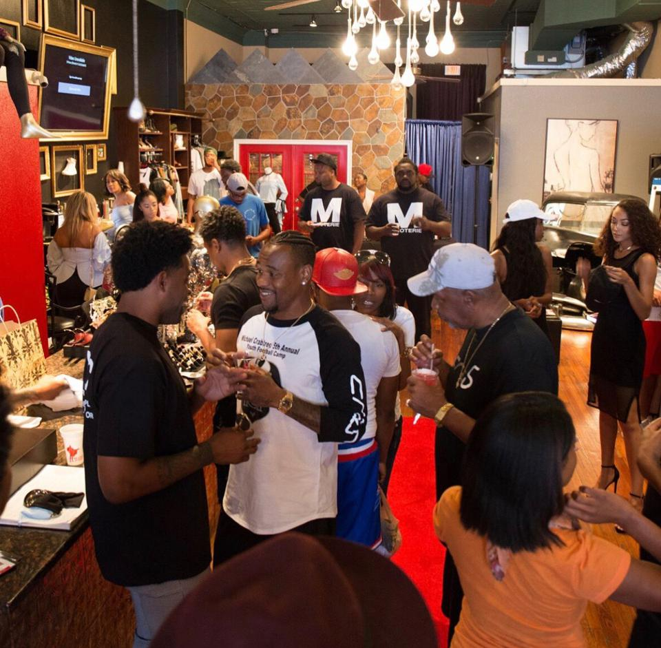 People enjoying their time at an event being held at Guns & Roses Boutique.