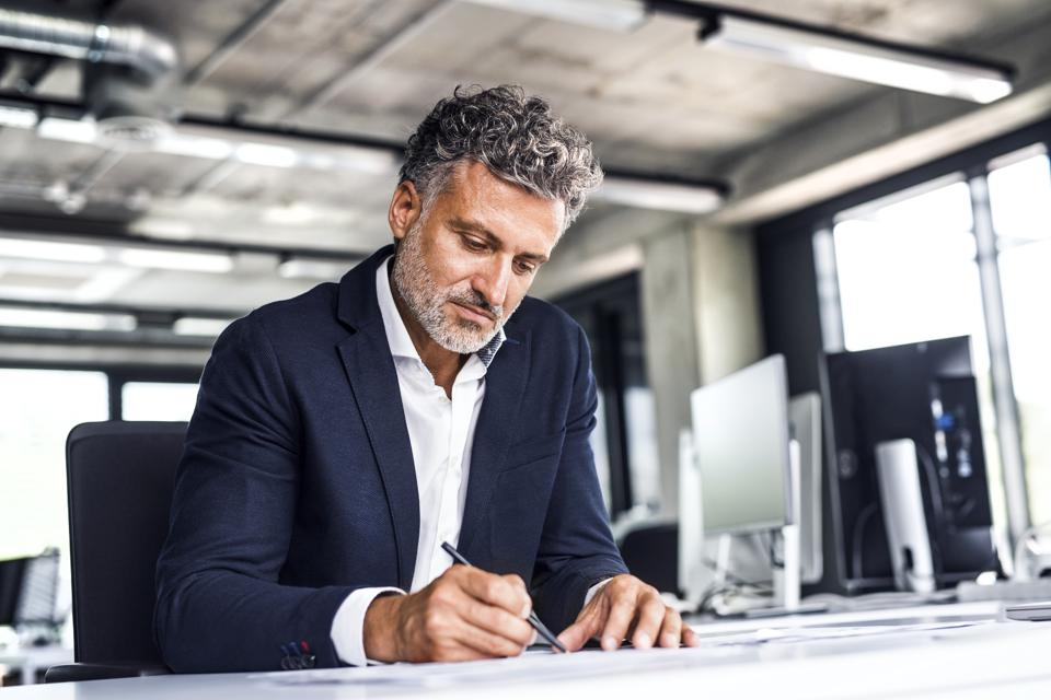 Mature businessman writing at desk in office