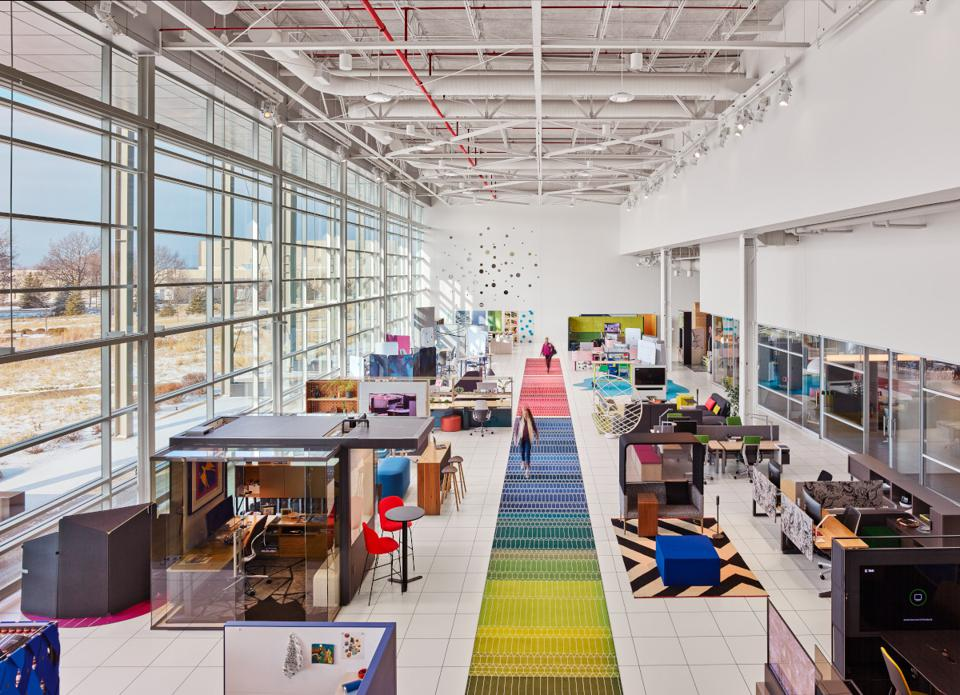 High view of modern office with bright colors and view to outside. The office is critical now for engagement, innovation and experience--and cannot go away.