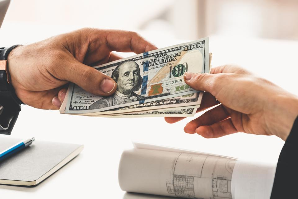 Businessman hand sending money to another business person. Transaction, payment, salary and banking concept.