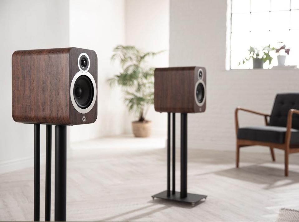 A pair of Q Acoustics 3030i speakers mounted on speaker stands