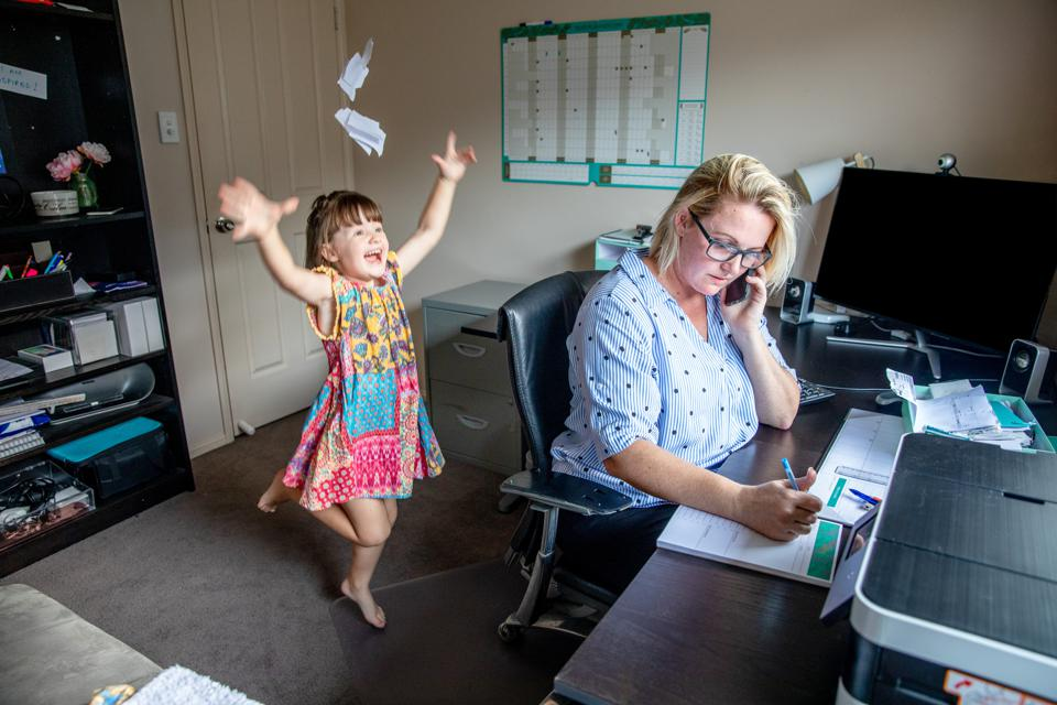 Set boundaries between work and home - evidently needed as female professional talks on phone and takes notes in a crowded home office while young child plays in the background