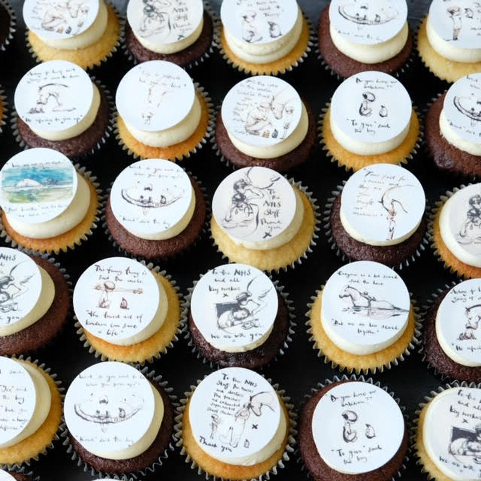 A selection of cupcakes made my baker Emma Dodi topped with illustrations by artist Charlie Mackesy