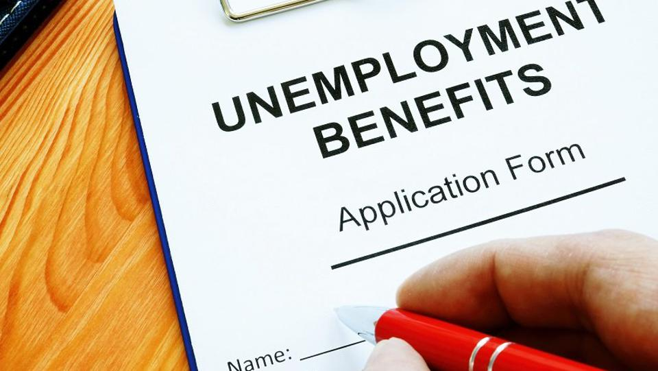 person filling out unemployment benefits forms