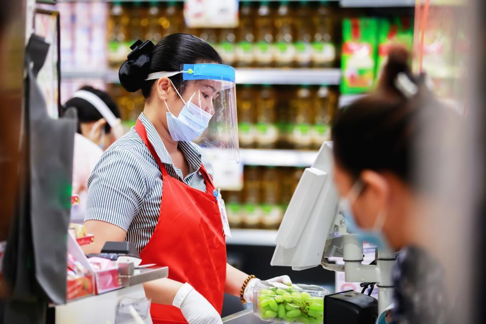 female supermarket cashier in medical protective mask working at supermarket