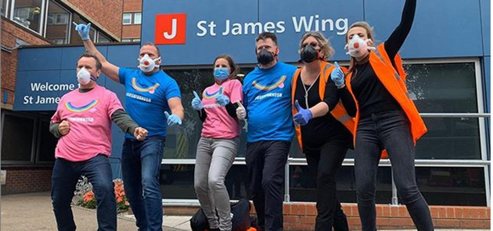 A team of people wearing face masks standing outside St George's Hospital after delivering food to frontline NHS staff.