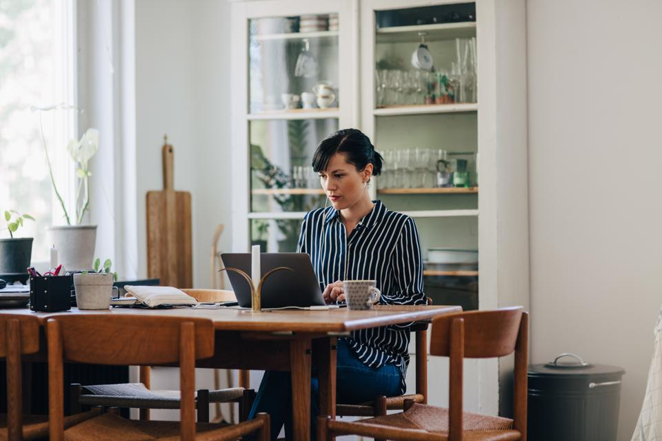 Mid adult businesswoman using laptop at table while working in home office