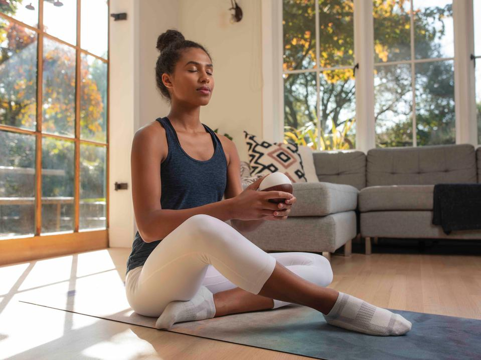 A young woman sits cross-legged meditating on a yoga mat with a white egg-like device