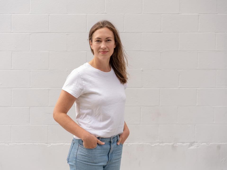 McDevitt, in a white t-shirt, stands in front of a white wall.