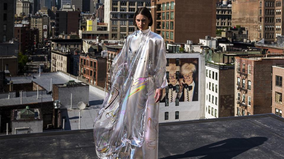 A woman stand on top of a building wearing a virtual dress.