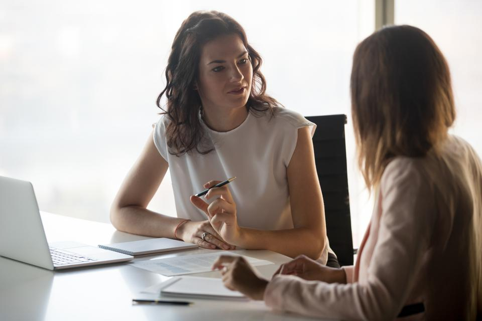 Two diverse serious businesswomen talking working together in office