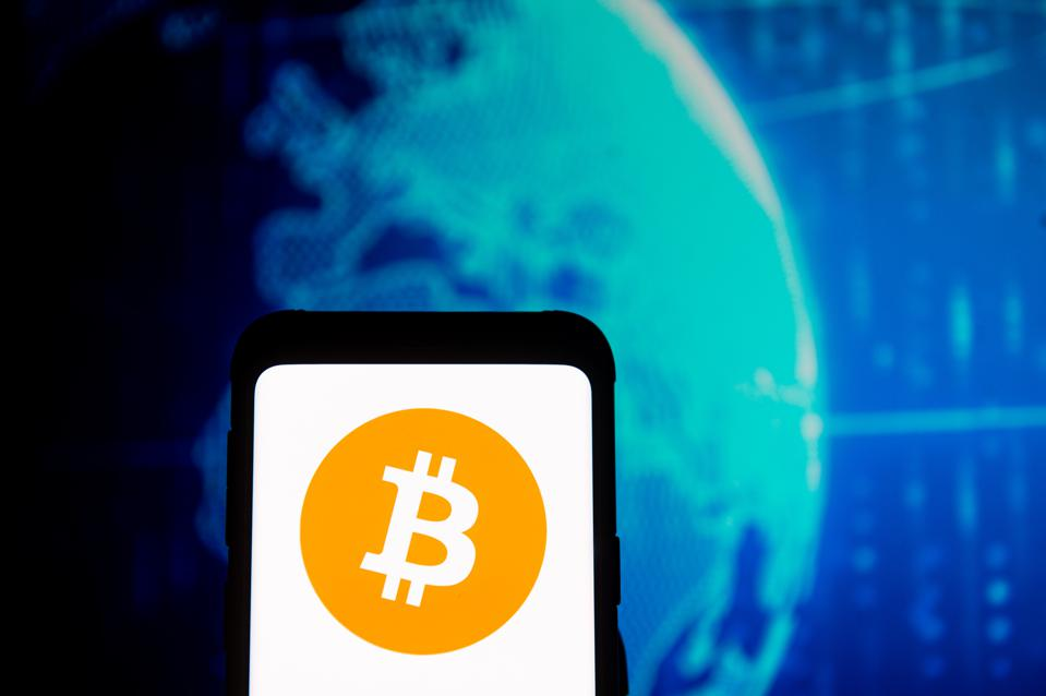 In this photo illustration a Bitcoin logo seen displayed on...
